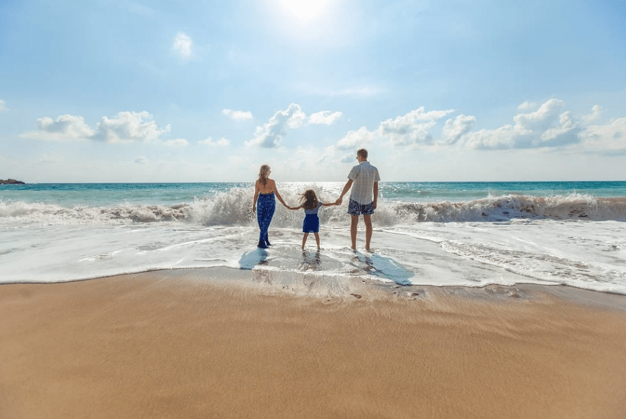 parents with their daughter holding hands together on a beach